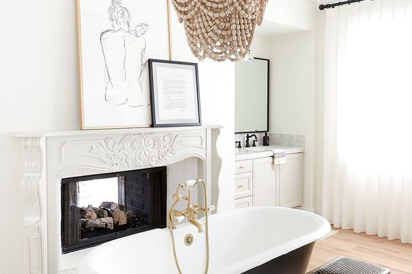 A sleek white bathroom with a black bathtub and a beaded chandelier