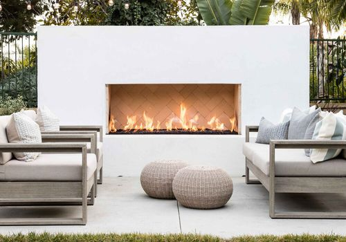 A white outdoor fireplace, situated on a matching white deck