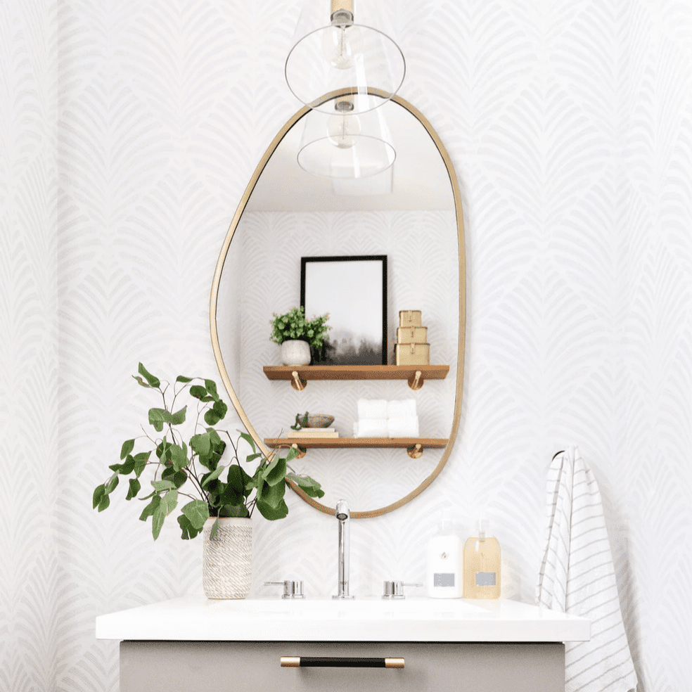 A powder room with a fun mirror and textured wallpaper