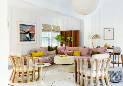 Studio apartment with white walls and pink sectional sofa.