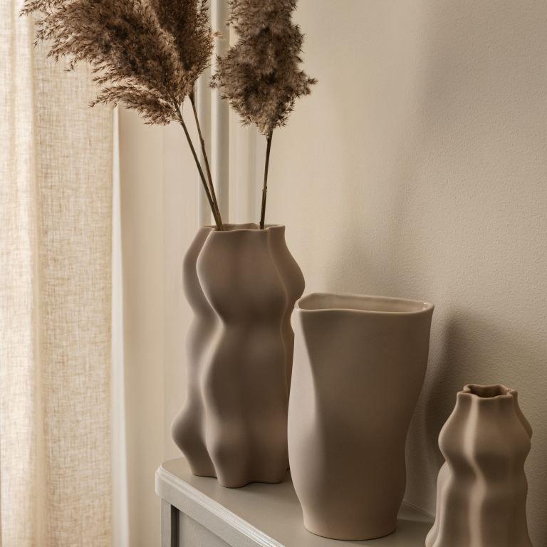 Small ceramic vase on fireplace mantle.