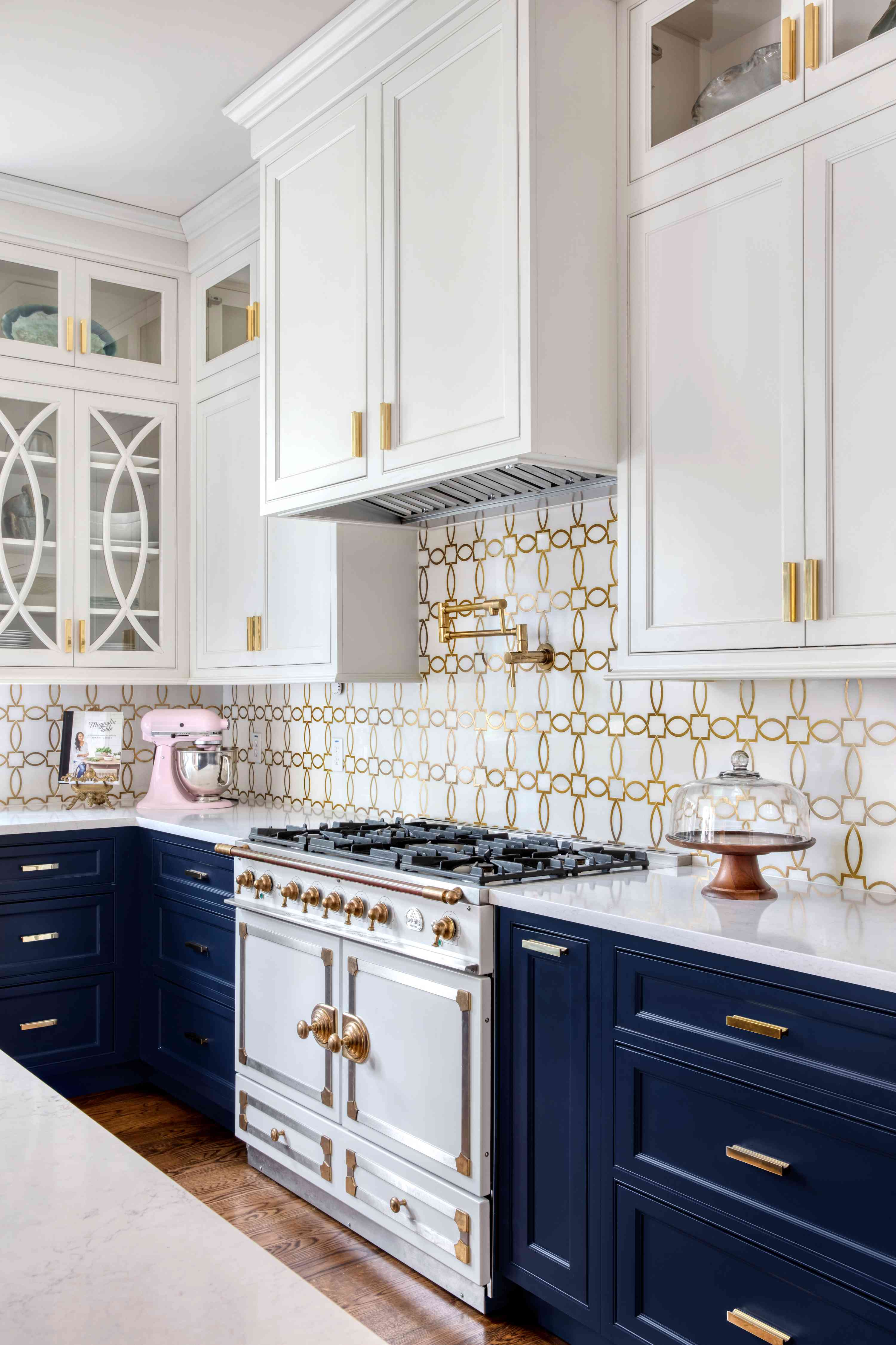 Gold and white backsplash in navy and white kitchen