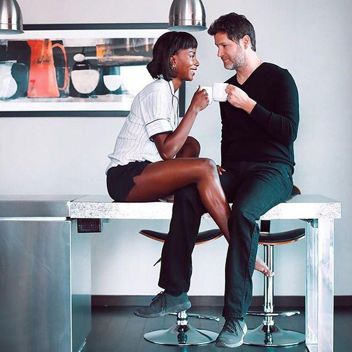 una pareja tomando un café con las piernas entrelazadas
