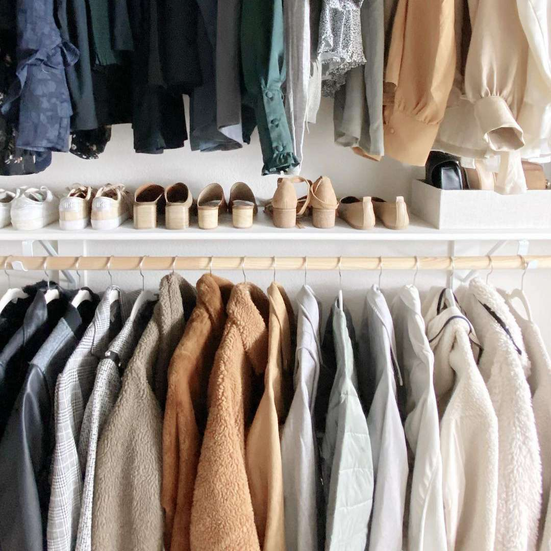 Organized closet with neutral clothing.