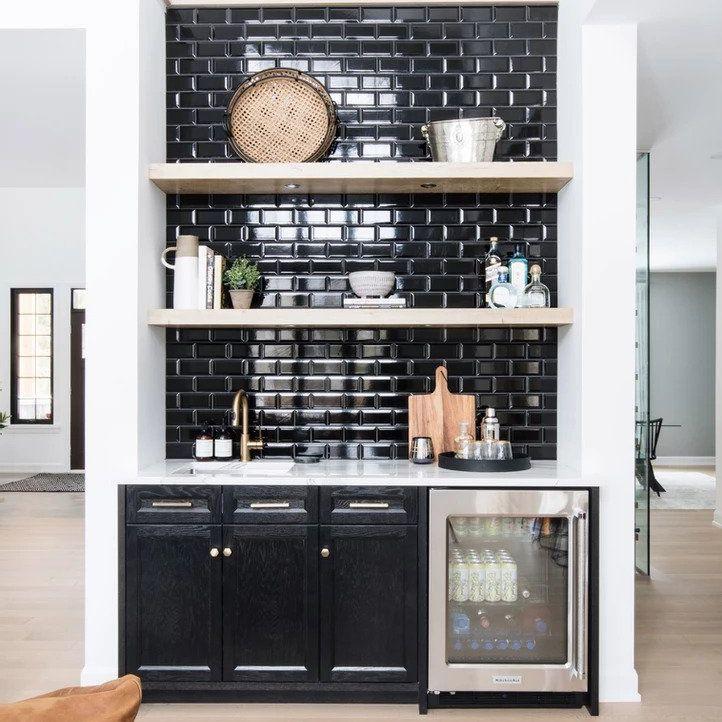 At-home bar features black subway-tiled backsplash, exposed shelves, mini-fridge
