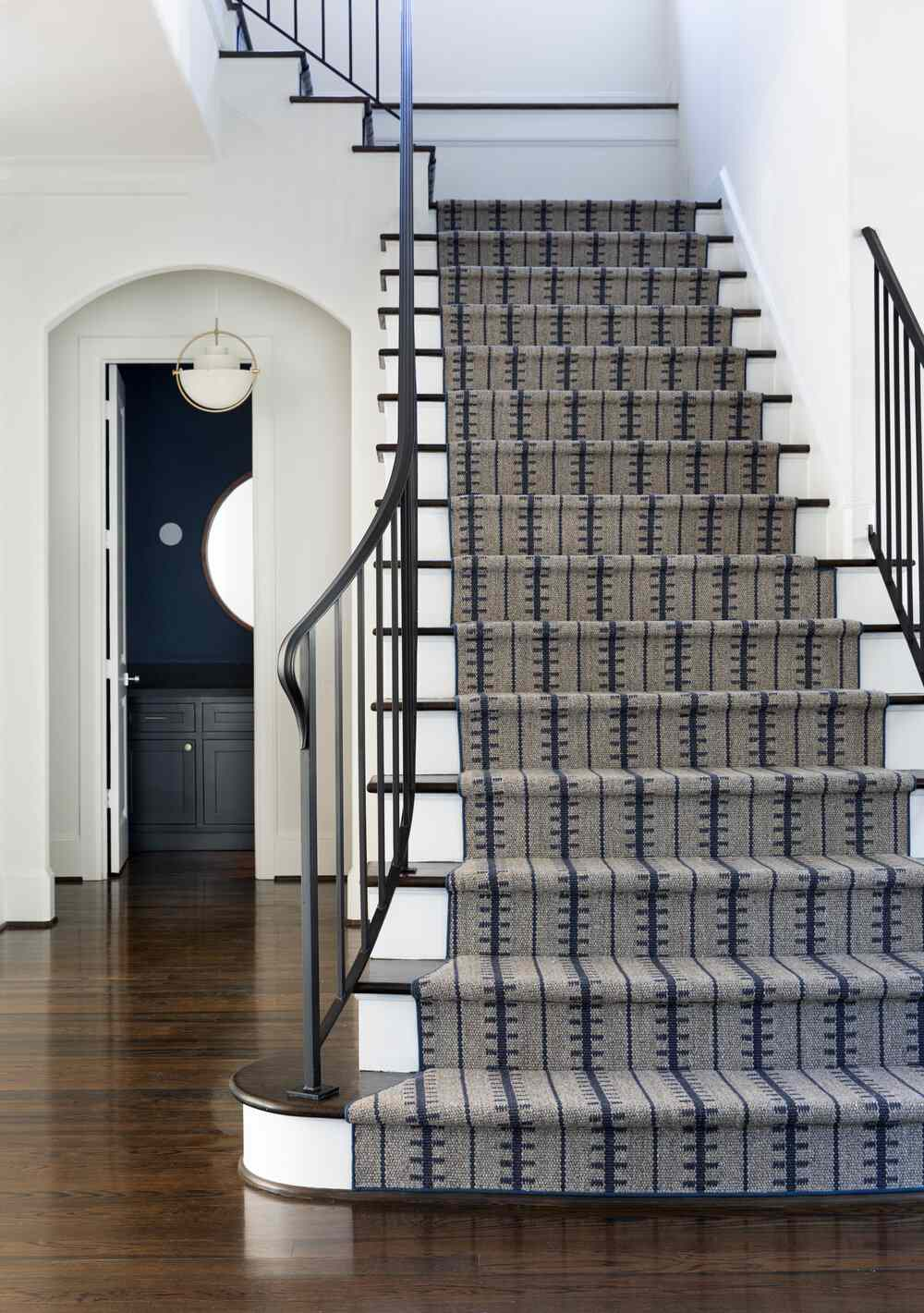 A staircase lined with gray and navy printed upholstery