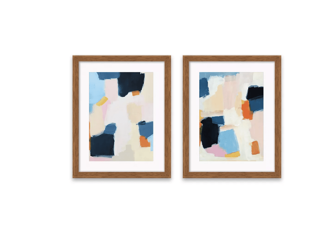 A set of two identical framed abstract prints with white mats.