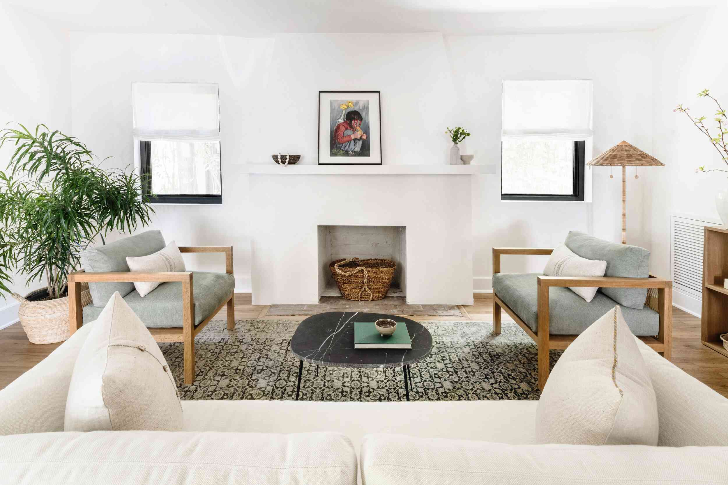 Living room with all-white fire place, white couch, patterned area rug