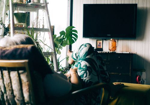woman in front of TV in plant-filled apartment