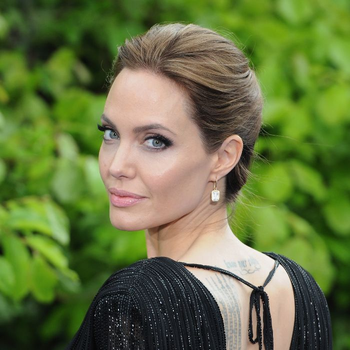 Angelina Jolie with an updo wearing a black dress and looking over her left shoulder.