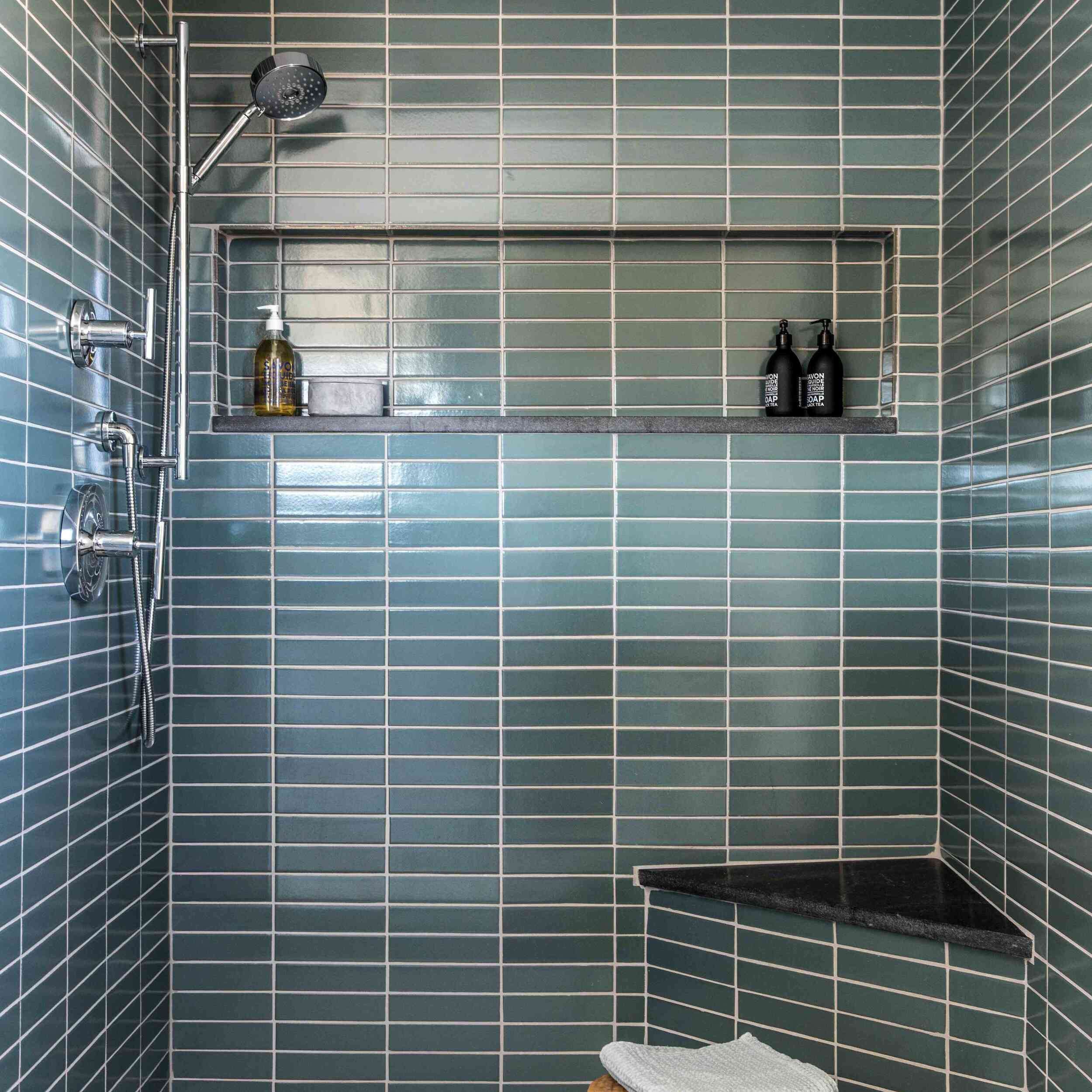 A shower lined with forest green tiles