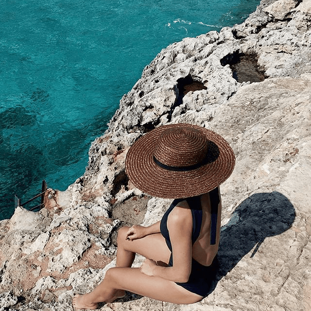 A view looking down on a woman sitting on a cliff sunbathing and looking into the clear water below.