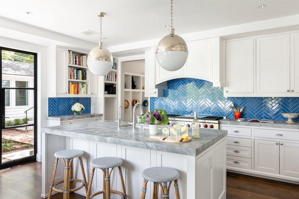 White kitchen with bright blue backsplash.