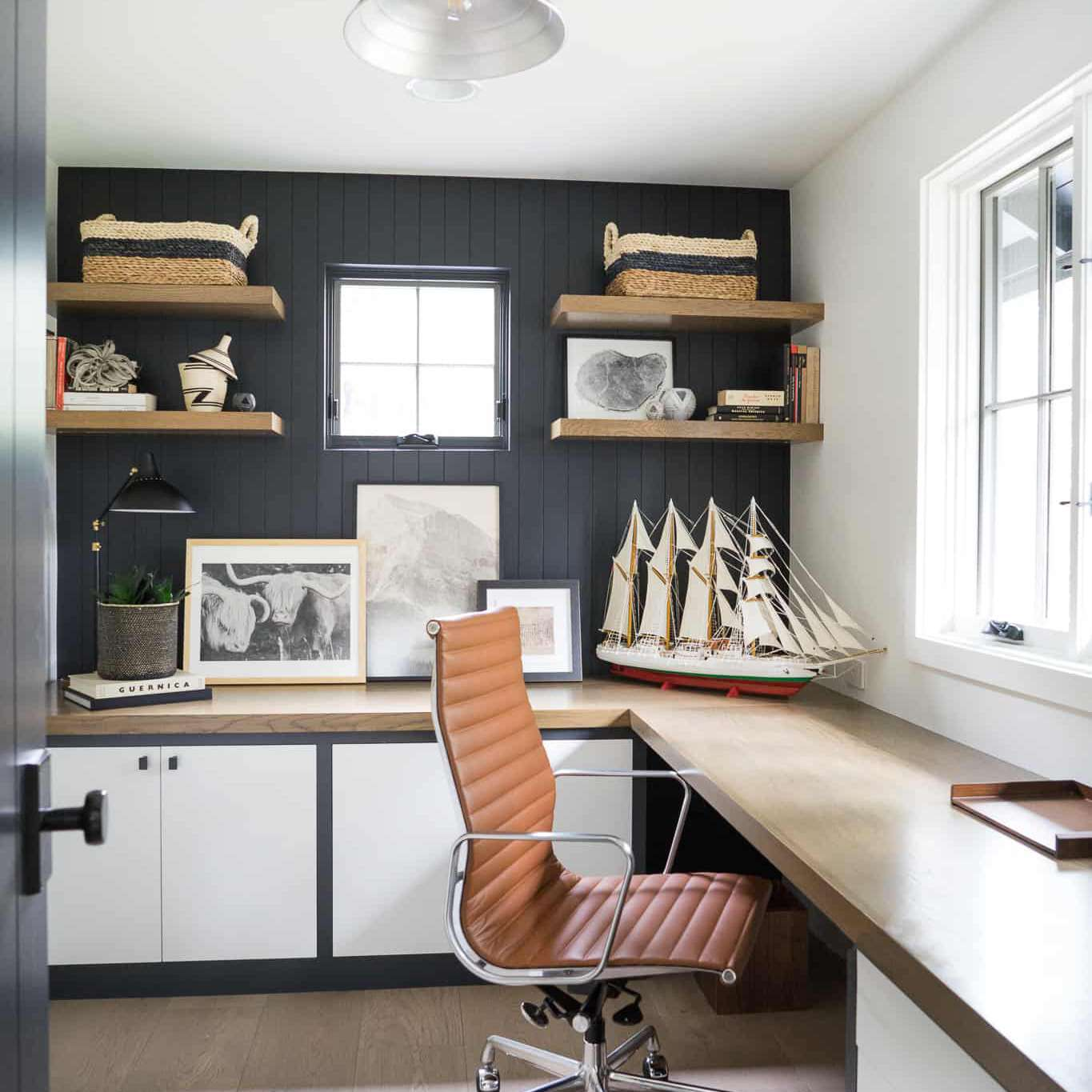 A home office with a wraparound wooden desk that covers two full walls