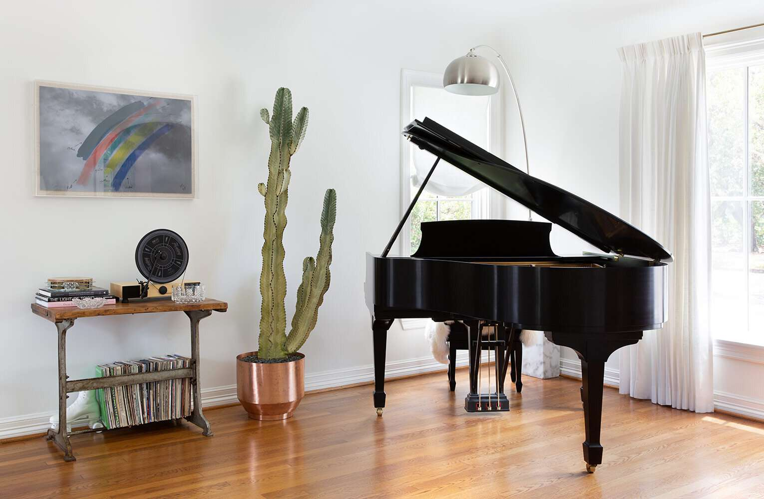 A living room decorated with sparse decor, including a piano and several metal pieces