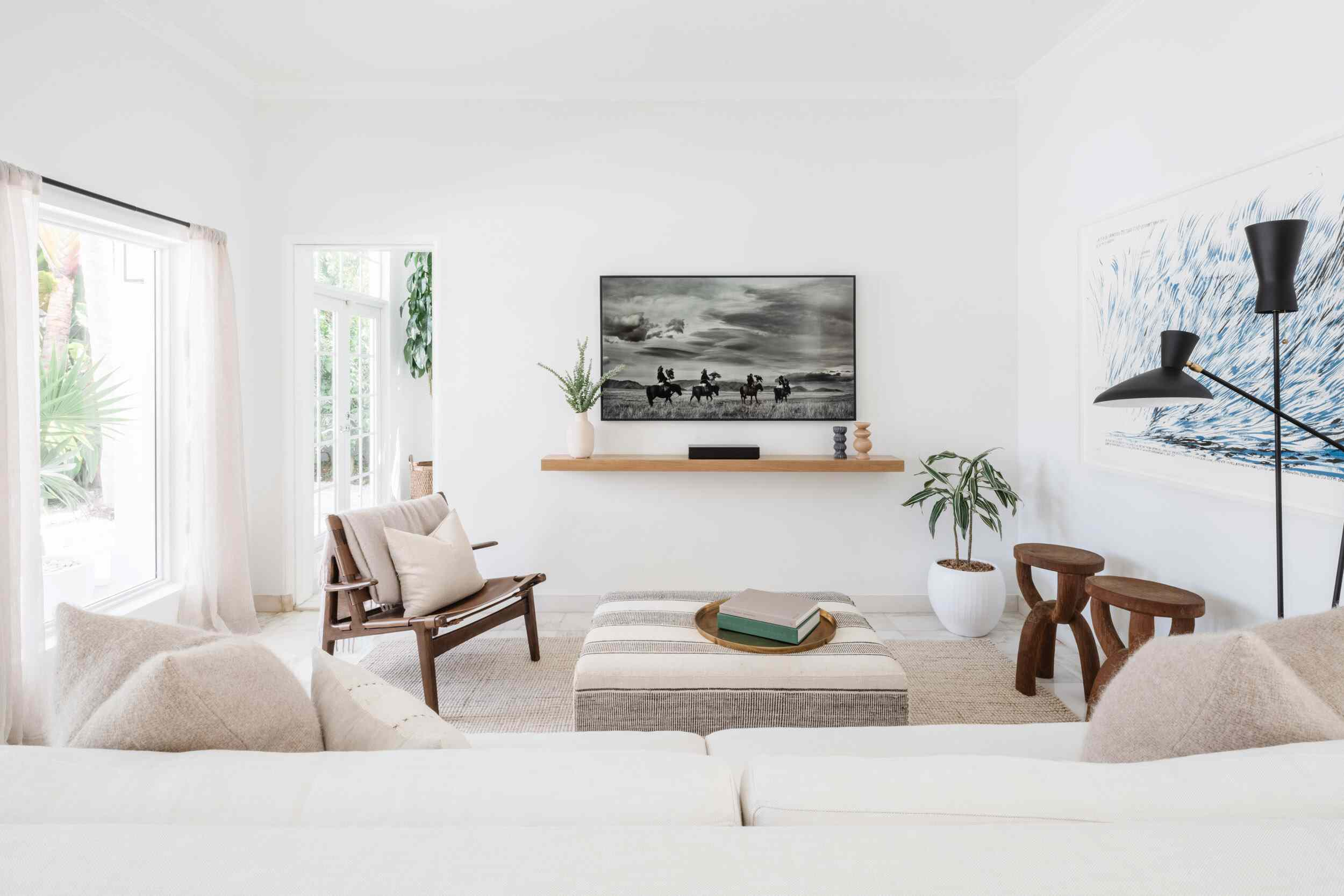 A mostly white living room with a black-and-white poster that looks slate gray from afar