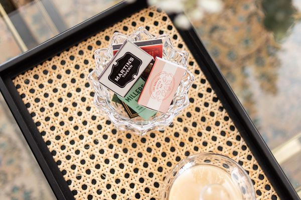 Books of matches in a glass bowl on a cane tray.