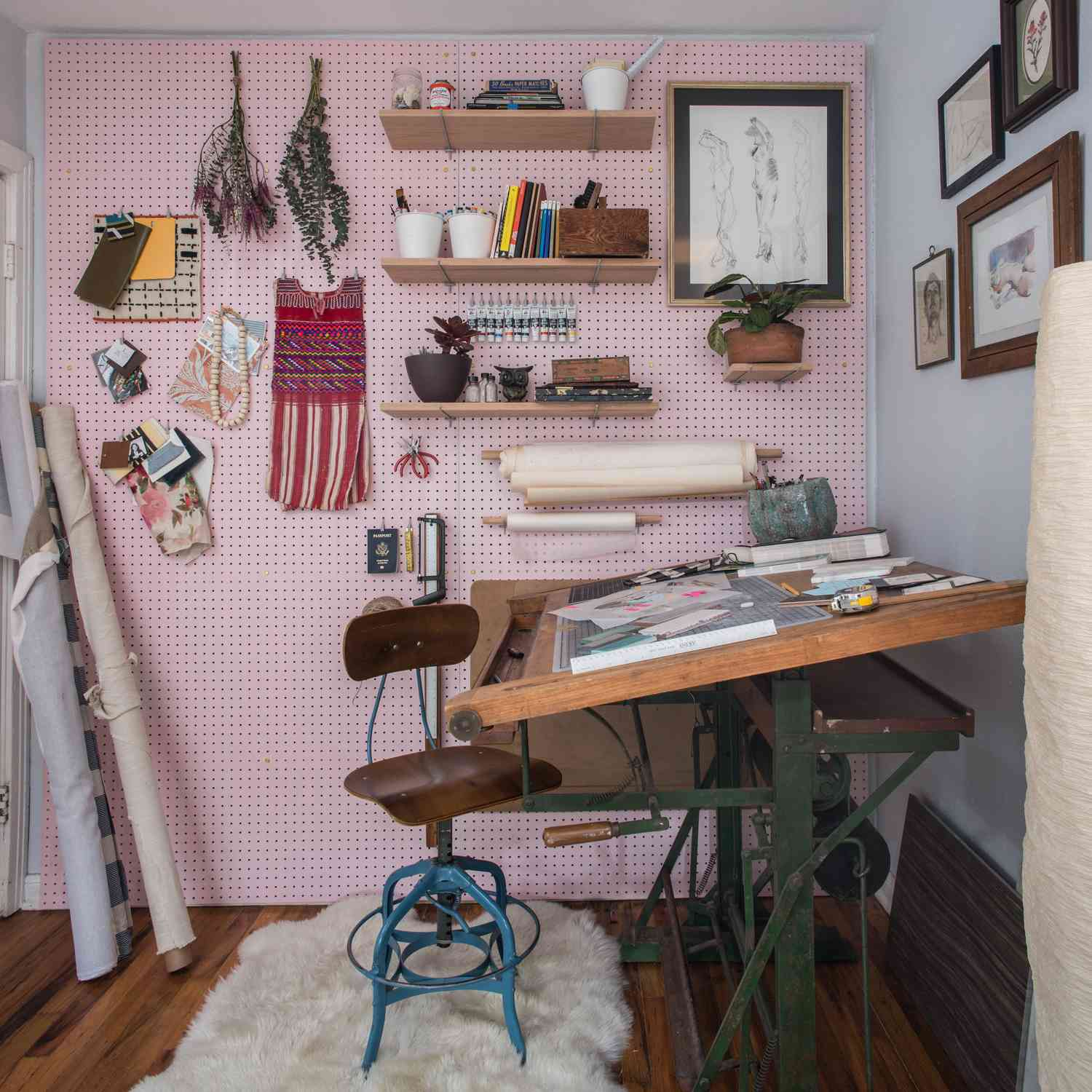 A craft room with a pastel pink pegboard panel wall