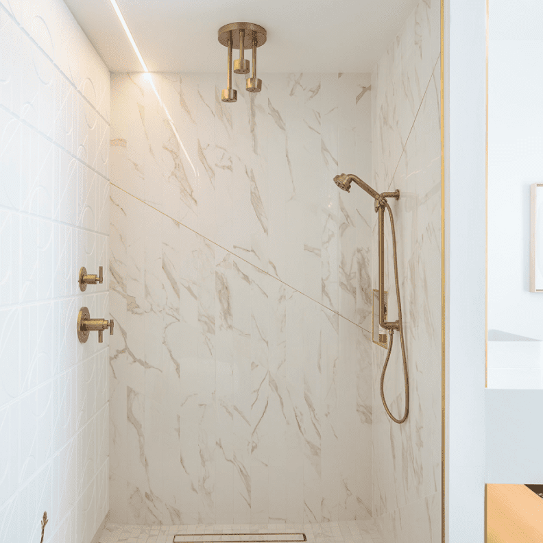 A bathroom shower lined with off-white marble