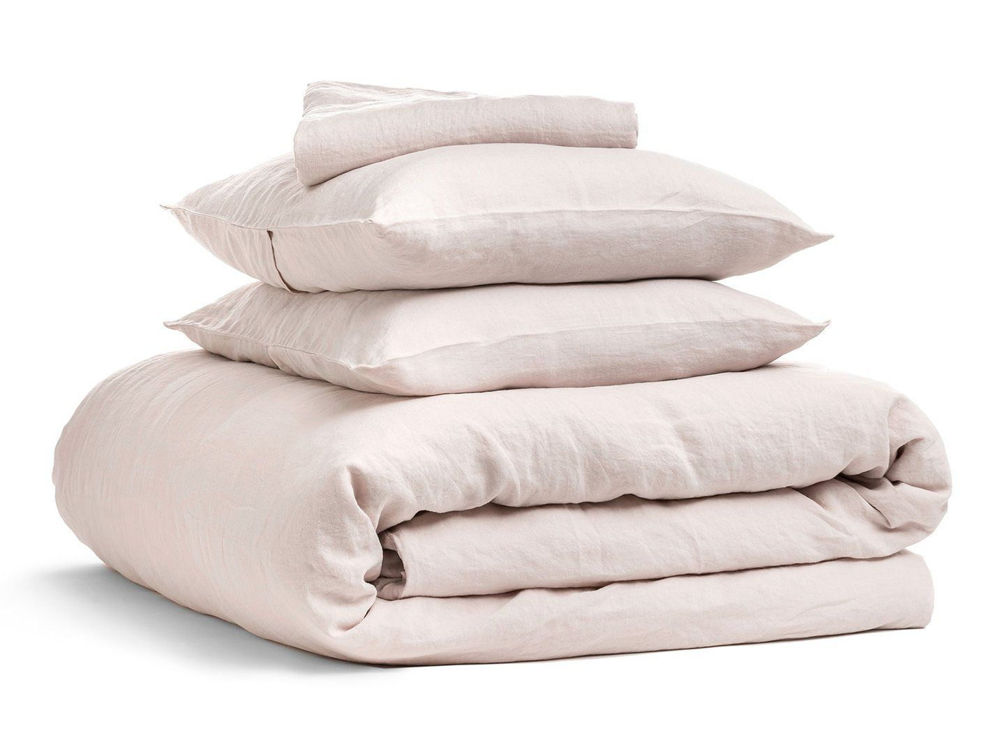 A set of pink linen bedding with two pillows, a top sheet, and a duvet cover.