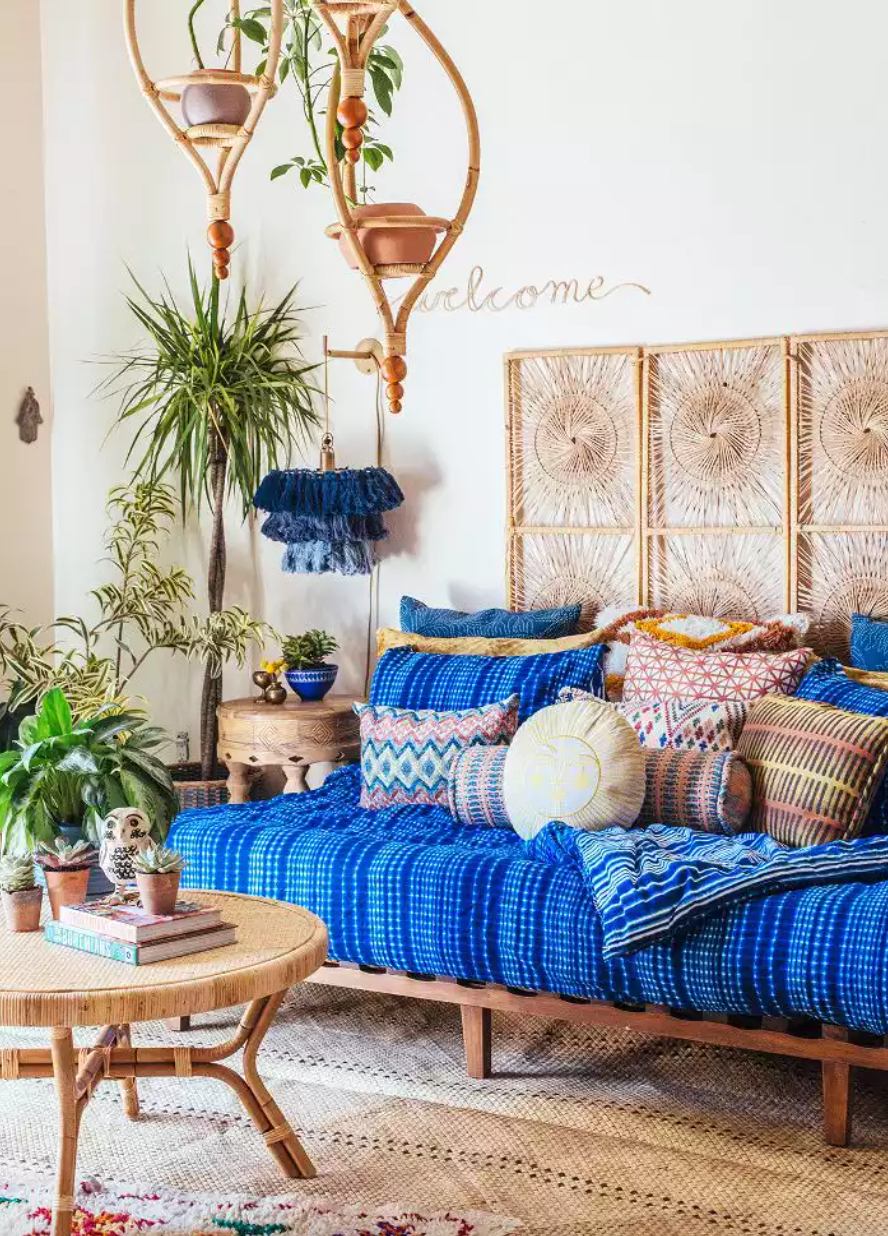 Bohemian-inspired living room with blue patterned textiles and hanging planters