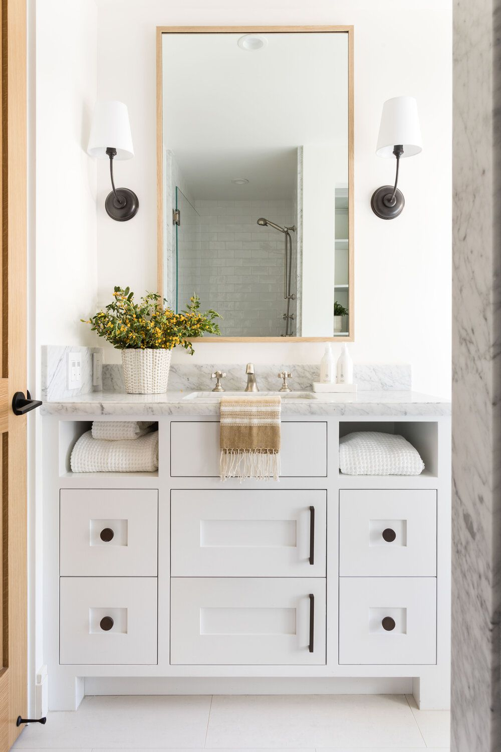 A small primary bathroom packed with small drawers and cabinets
