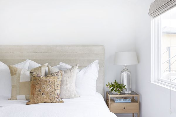 An ivory bed with several throw pillows