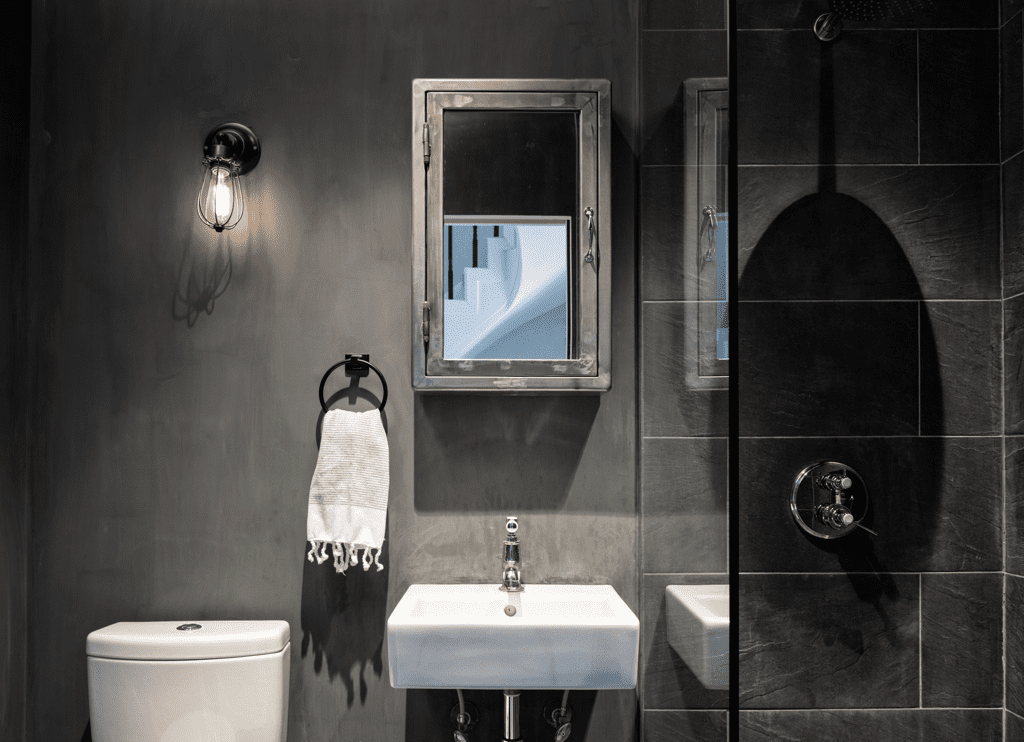 bathroom with black tile and concrete style wall