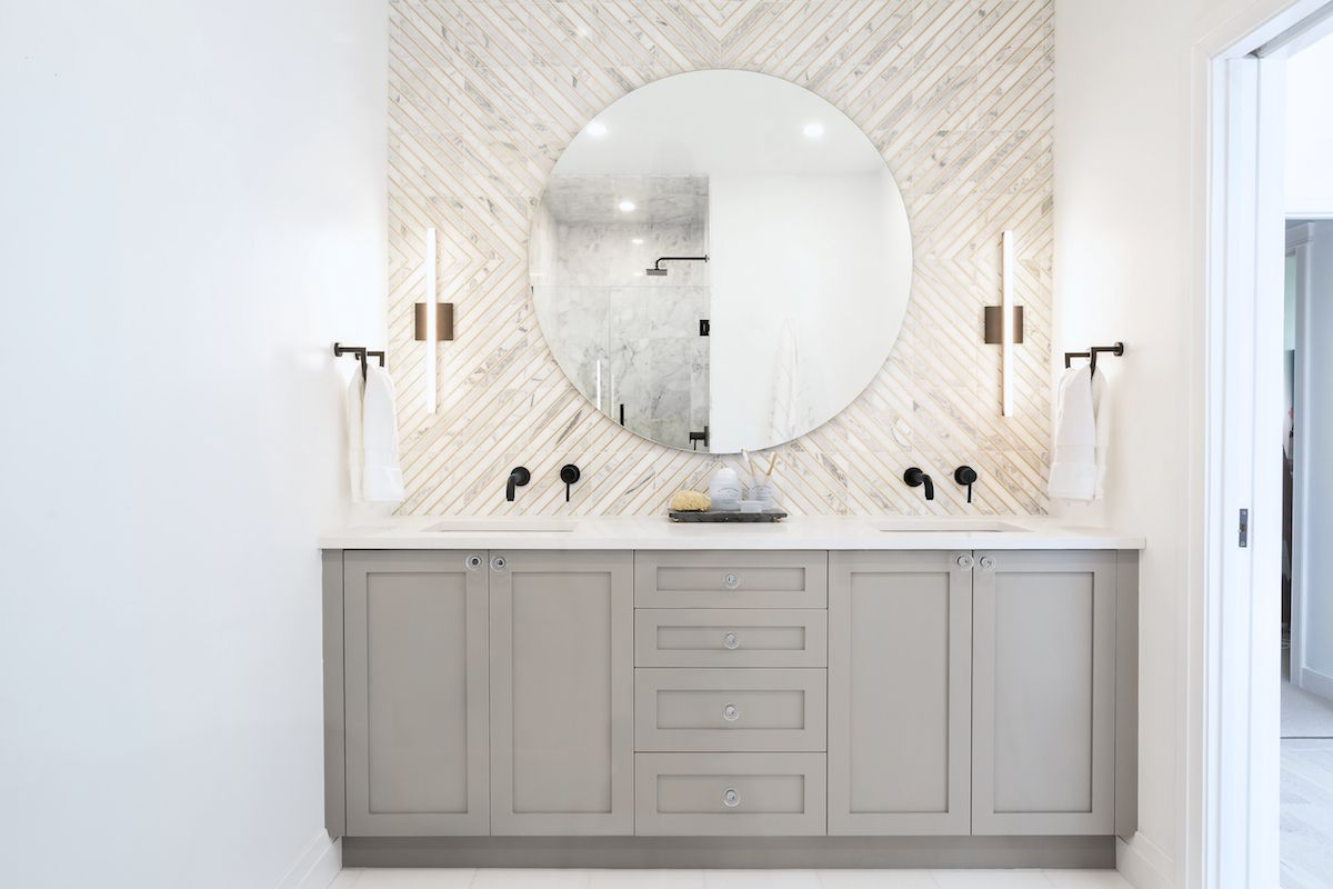 A bathroom with gray cabinets and a white tile-lined wall