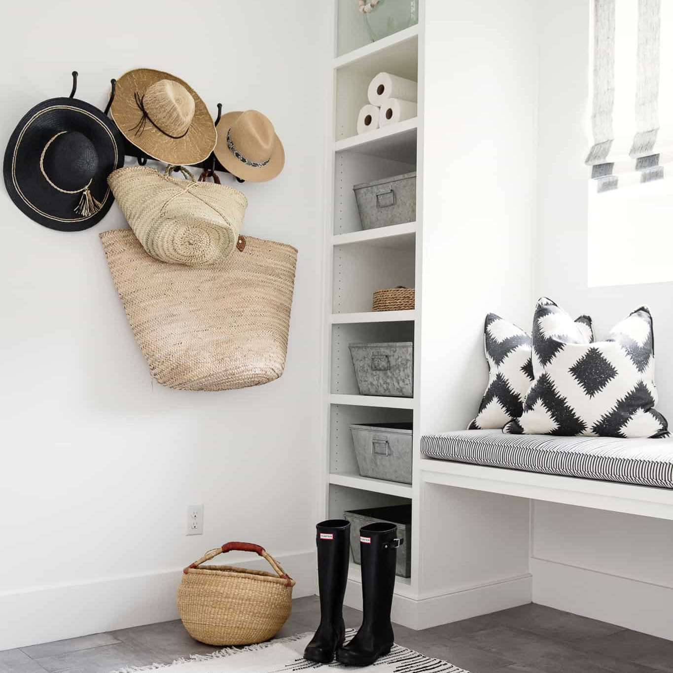 An all-white mudroom with a bench, several shelves, and some hooks