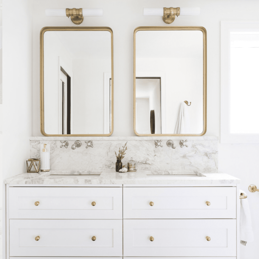 Double vanity with gold mirrors.