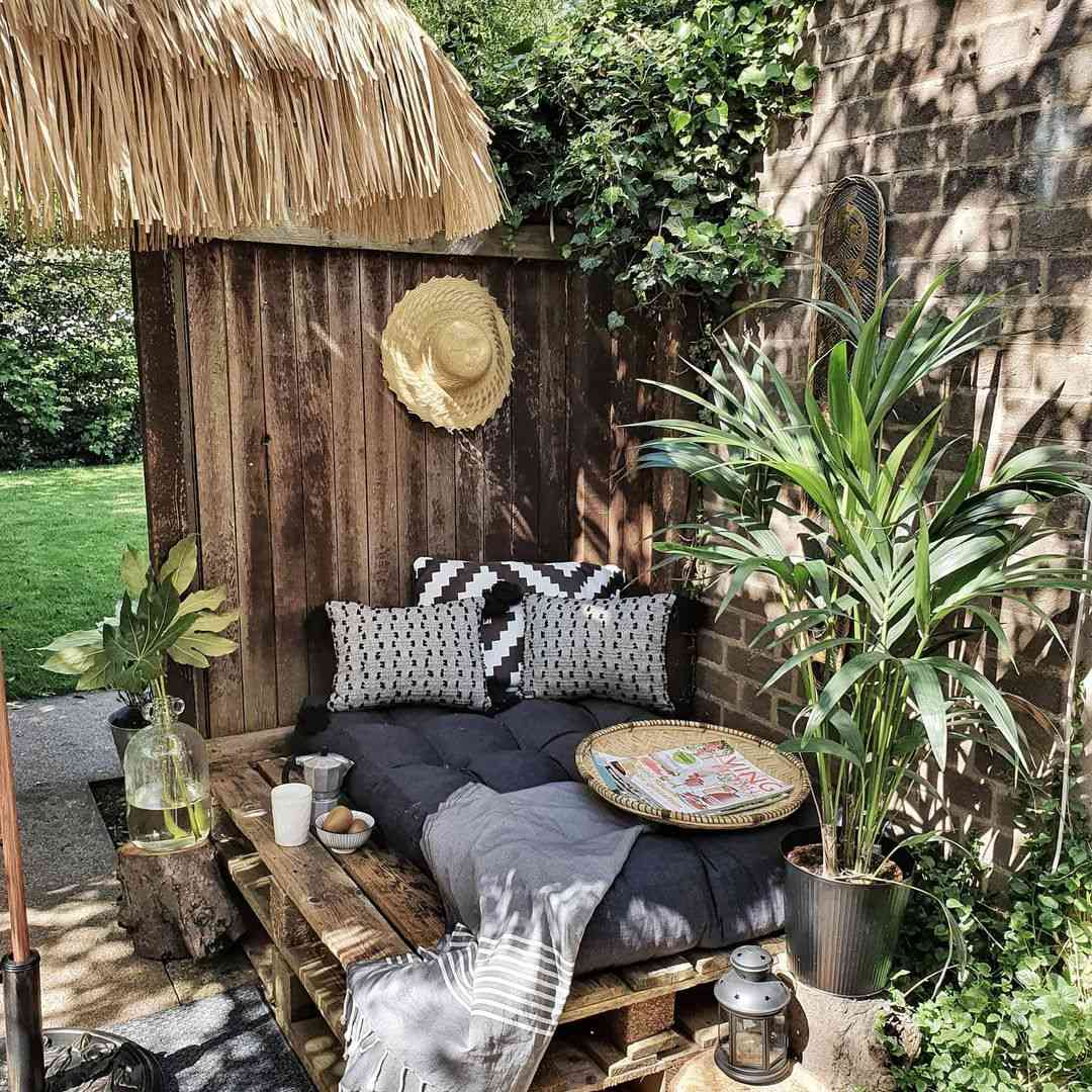 Outdoor nook with daybed and plants.