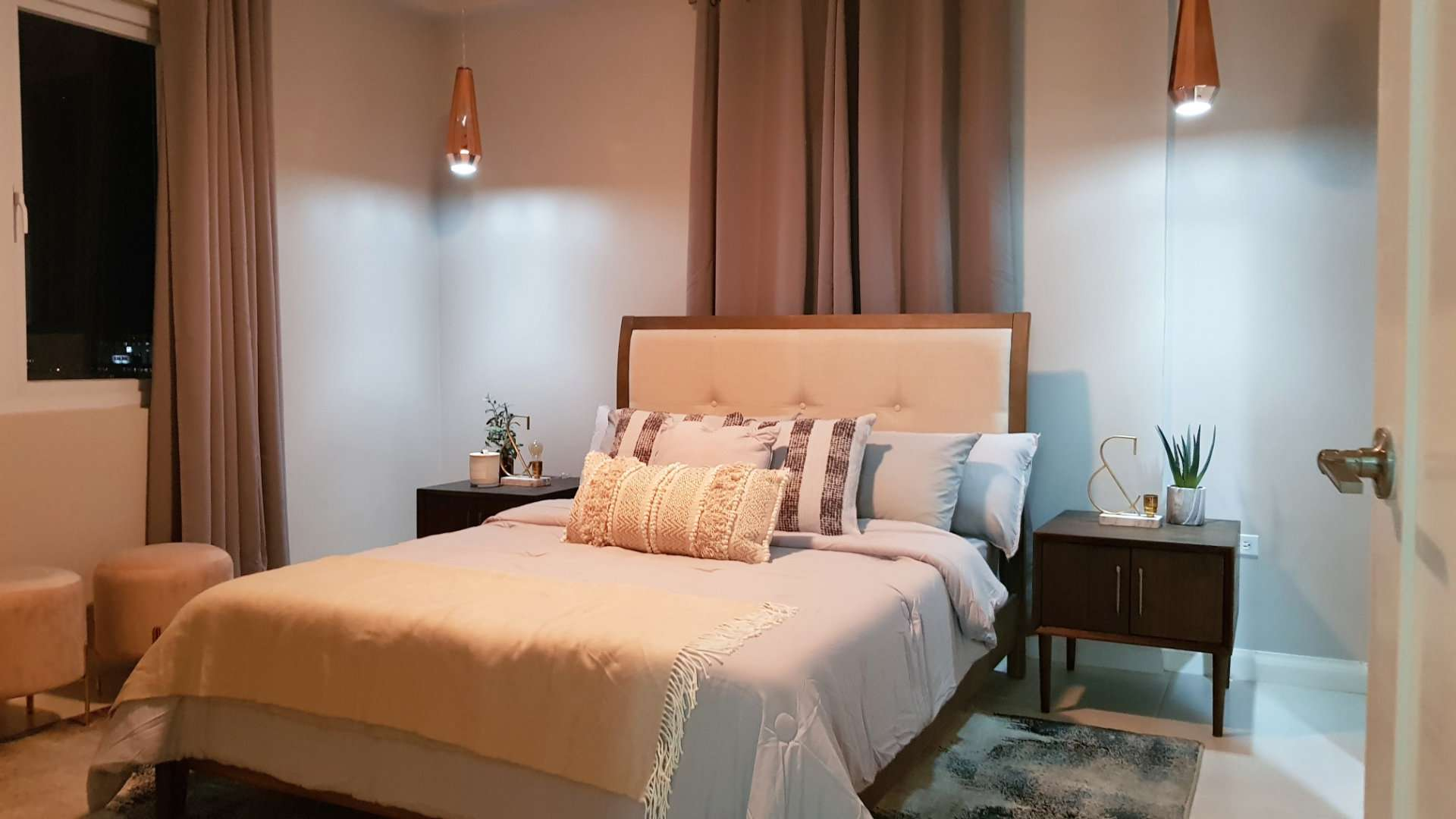 A bedroom with two pendant lights on either side of the bed.