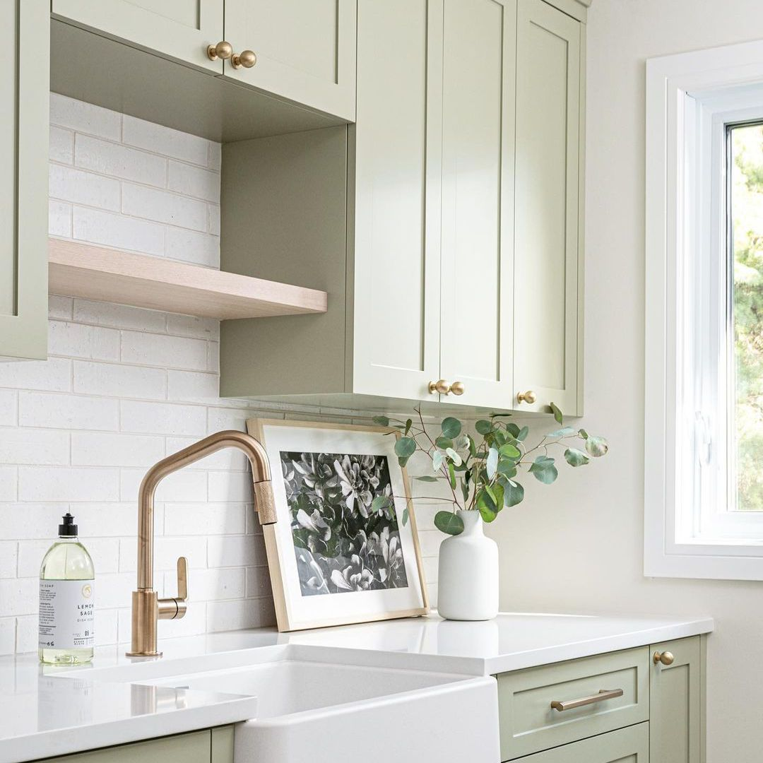 Laundry room with light green cabinetry