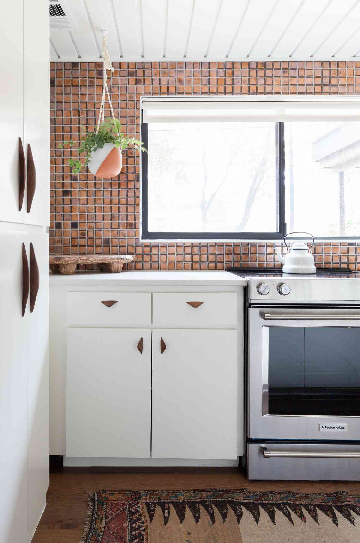 A kitchen with a vibrant backsplash and a printed rug
