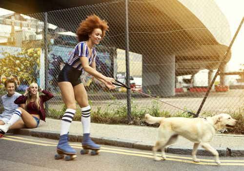 Woman rollerskating with dog