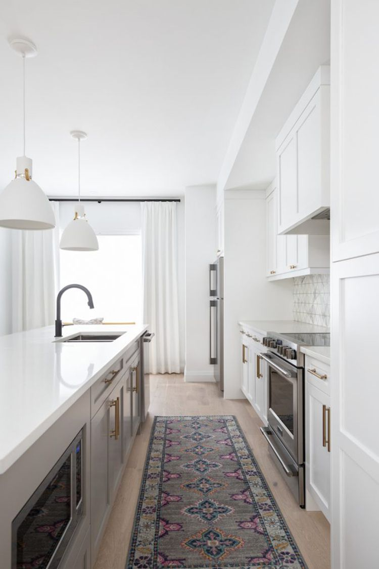 A white kitchen with a gray printed rug