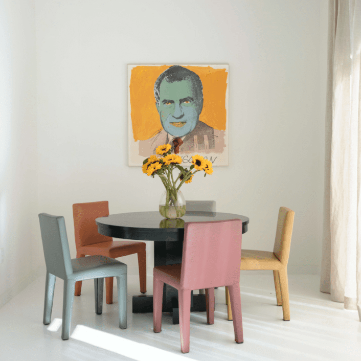 A table surrounded by colorful chairs, next to a work of modern art