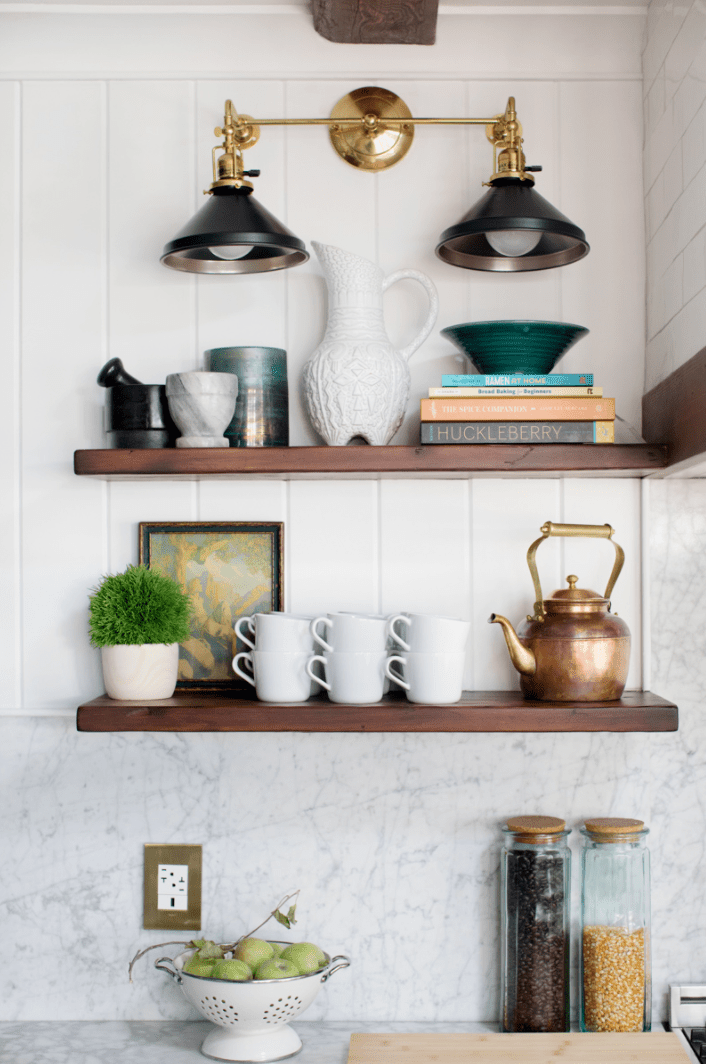 A kitchen with wooden shelves and a farmhouse lighting fixture