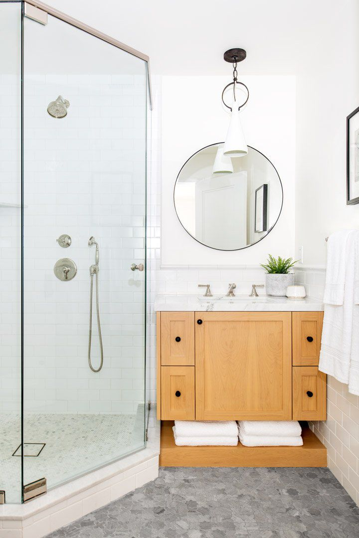 A small primary bathroom with a hexagonal shower tucked next to a vanity