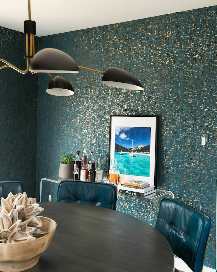 After picture of dining room with moody teal wallpaper and leather chairs.