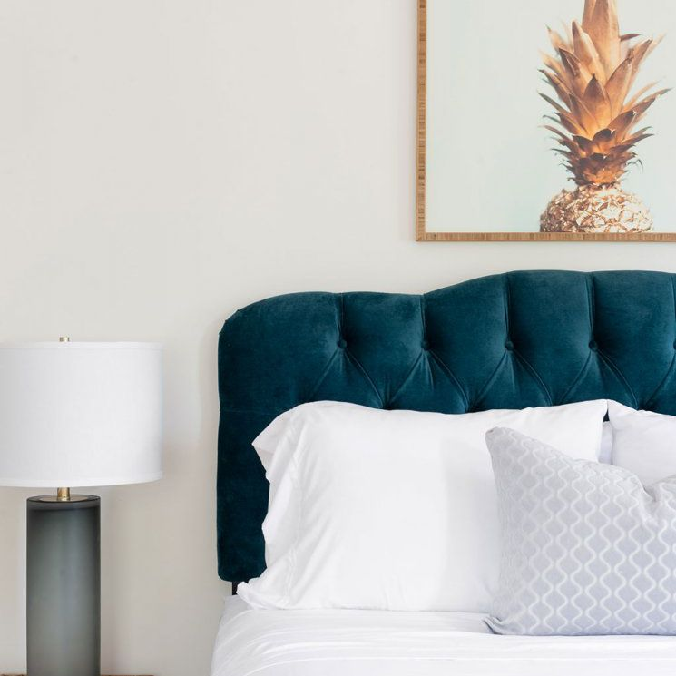Modern bedroom with light gray walls and blue and wood accents