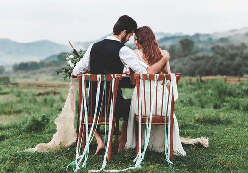 Vista trasera de la pareja de novios sentados en sillas en la granja