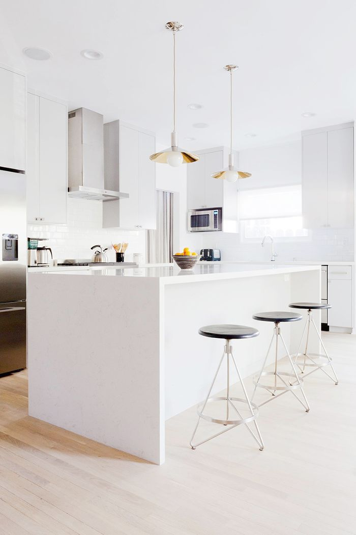 Sleek white kitchen with three round bar stools and pendant lighting