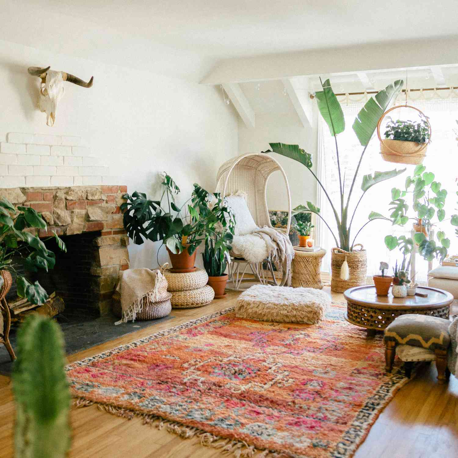 Boho chic living room overflowing with plants and cozy layers