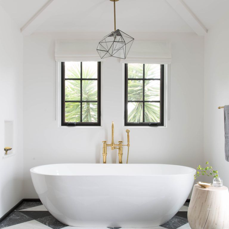 A master bathroom with a white tub and large, bold tiles