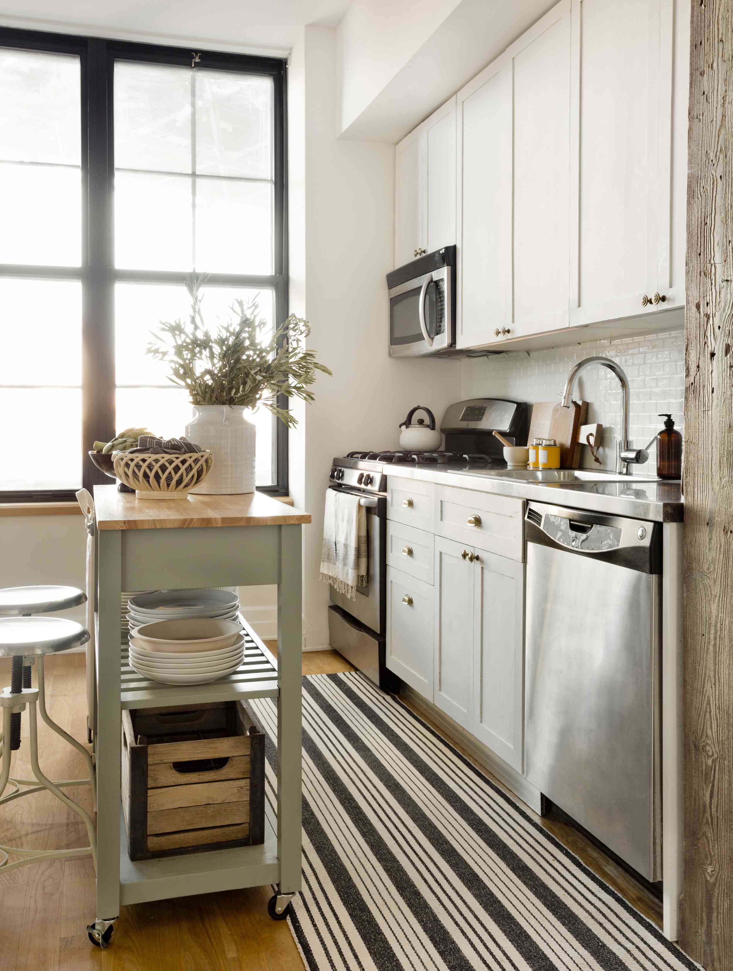 best kitchen ideas - galley kitchen with green rolling island and stools