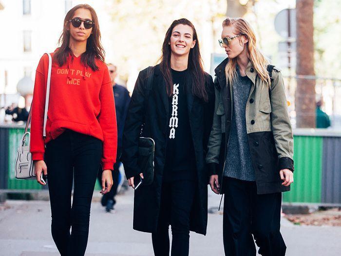 three smiling women walking down the street