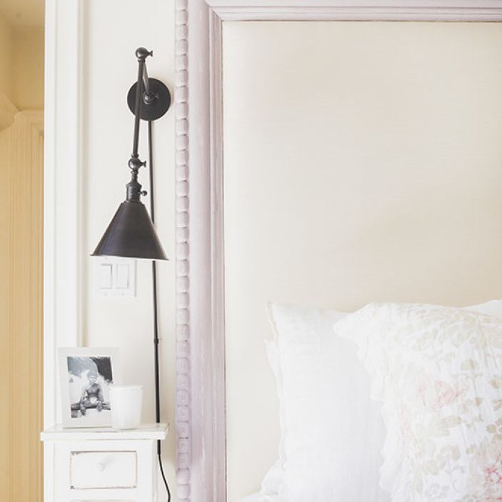 Bed with white bedding and light purple bedframe