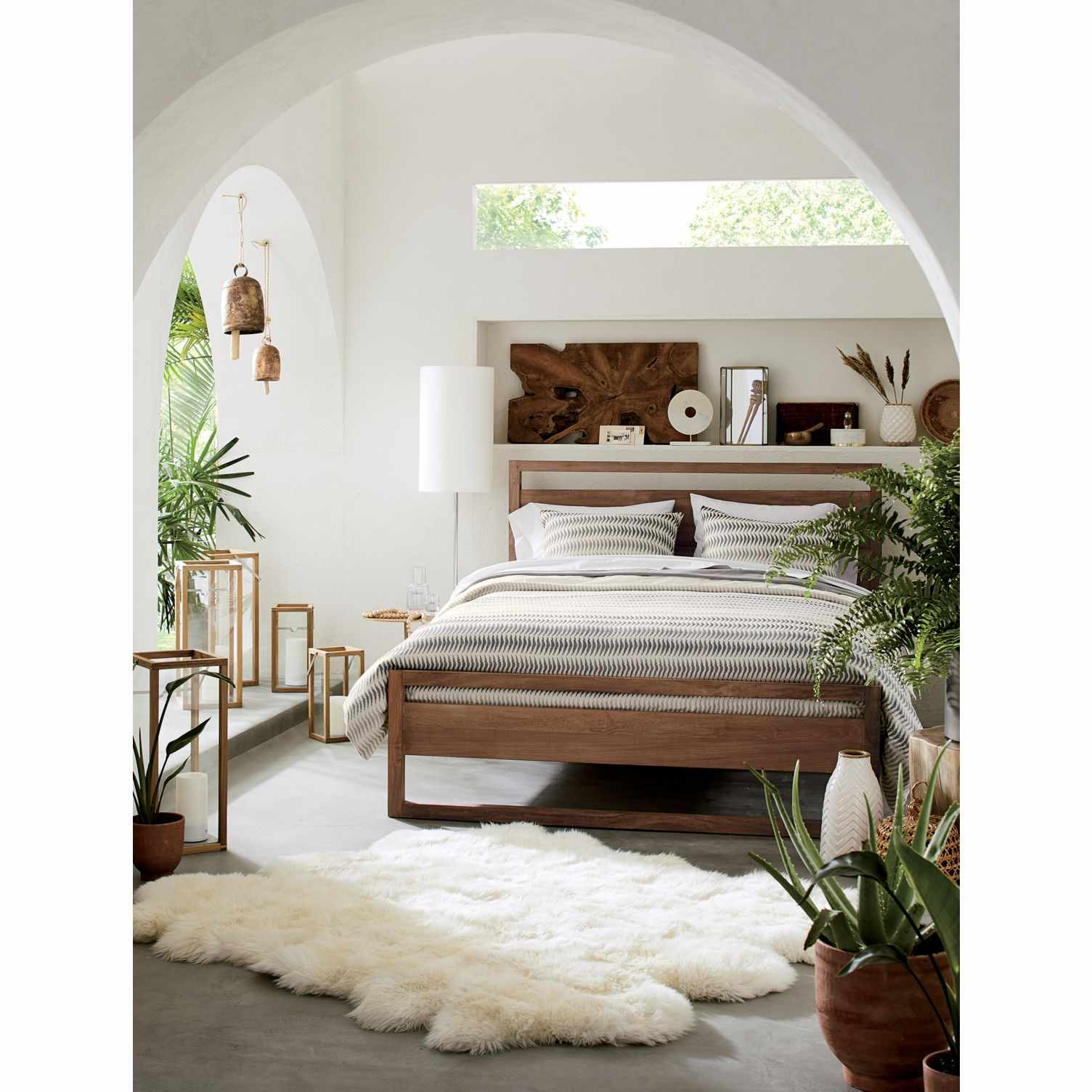 A sheepskin throw rug at the foot of a bed in a Mediterranean style bedroom.